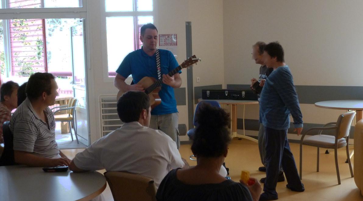 Raphaël Hiraboure jouant de la guitare et chantant au sein d'un pavillon de l'hôpital marin en présence de patients assis et debout