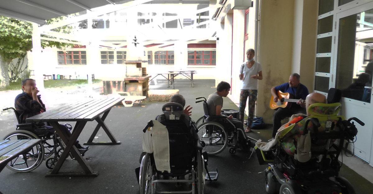 Le duo Palenka joue à l'extérieur du pavillon Camino à l'hôpital marin de hendaye, 4 patients (vus de dos) écoutent et réagissent aux musiques variées