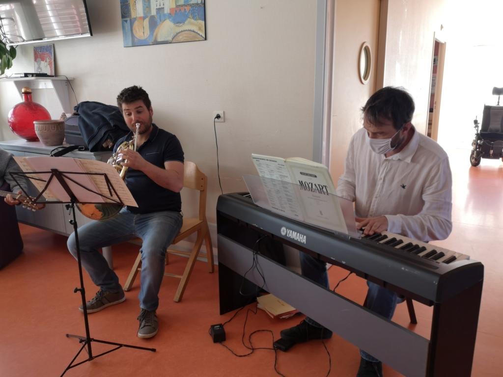 deux musiciens, arnaud guicherd et vincent planes jouent respectivement du cor et de l'orgue électronique