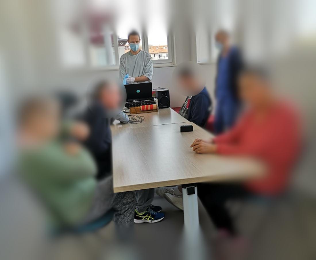 des patients (floutés) sont autour d'une grande table prêts à accompagner la musique lancée par Vincent notre animateur, afin de l'accompagner de diverses sonorités