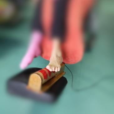 deux pieds d'une personne handicapée dont avec l'aide d'un pied elle fait tourner un rouleau pour produire de la musique, procédé de l'orgue sensoriel