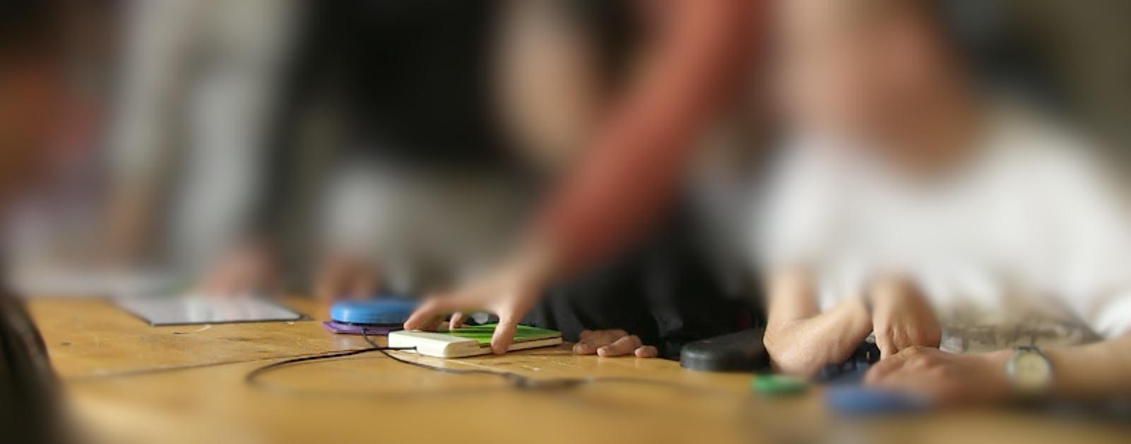 plusieurs personnes handicapées posent leur mains sur des contacteurs de l'orgue sensoriel pour pouvoir jouer et accompagner de la musique