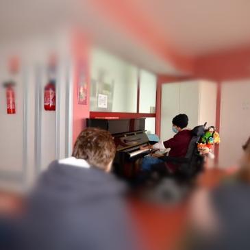 personne sur fauteuil roulant jouant du piano acoustique avec un public flouté
