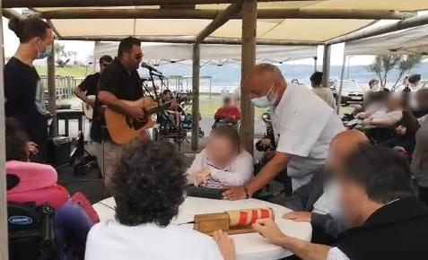 au 1er plan la table stido entourée des patients avec les différents contacteurs, au 2ème plan l'animateur stido et un agent puis musiciens et public