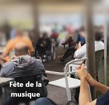 Au premier plan des mains qui applaudissent, puis un patient à la percussion et divers patients en fauteuil roulant qui assistent à la fete